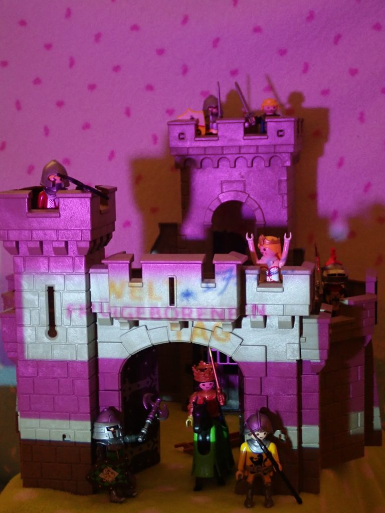 Spielzeugburg, lila angestrahlt und mit Schriftzug Weltfrühgeborenentag